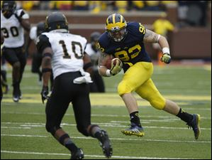 Appalachian State's A.J. Howard chases Michigan's Keith Heitzman.