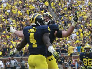 Michigan's De'Veon Smith, 4, is body bumped by Erik Magnuson during 2nd half at Michigan Stadium.
