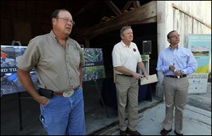 David Daniels, Ohio Department of Agriculture director, left, Jim Zehringer, ODNR director, and Craig Butler of the EPA, answer questions at a Wood County farm.