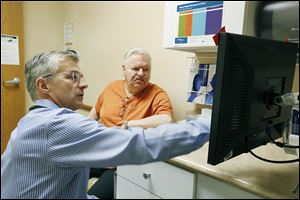 Dr. Mark Cockley confers  with one of his patients, John Petty of Perrysburg, in his office in Swanton.