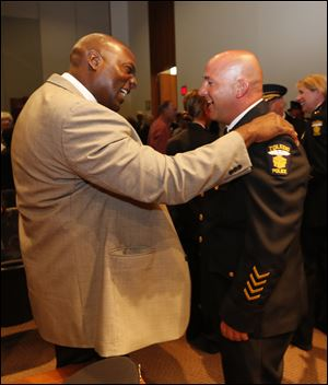 TPD Det. Perry Waddell, left, congratulates Capt. Ron Frederick upon his promotion. Det. Waddell also offered the invocation to the event.