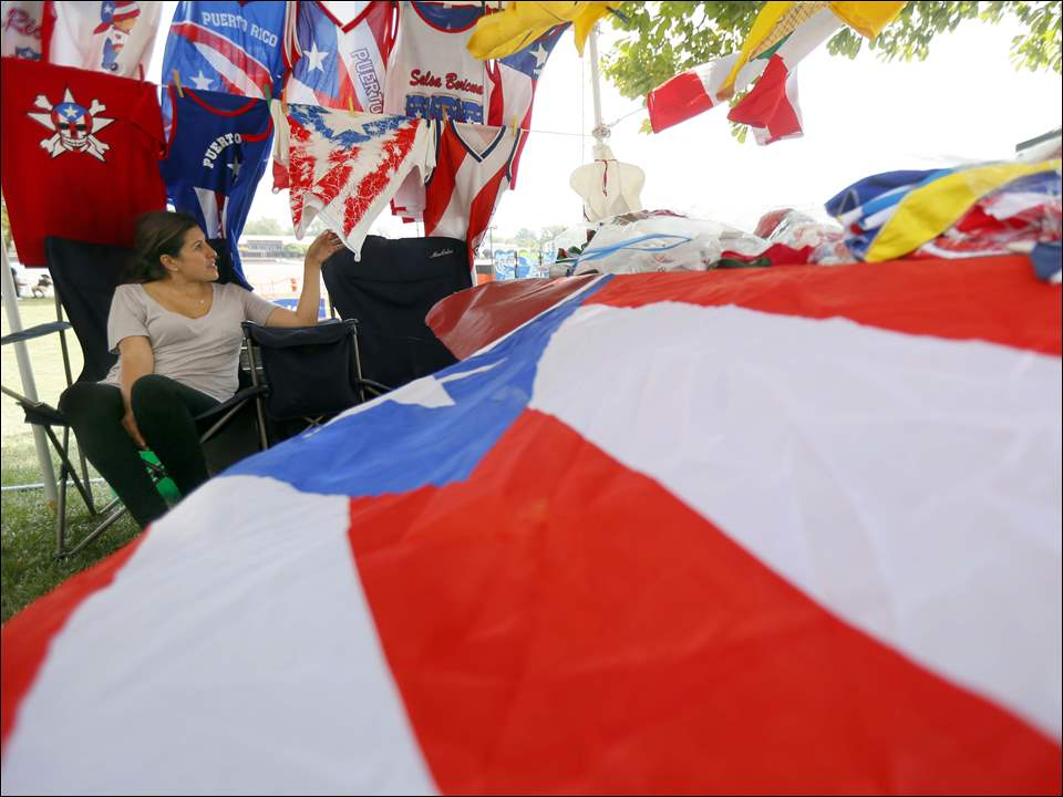 Jessica Guzman, from Chicago, reacts to the wind blowing the Puerto Rican flag and many of her Latino wares in her booth.