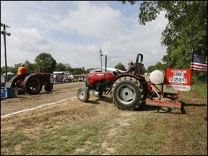 Jamie Zilles of Fremont watches as a competitor in the 5,500-pound weight class passes during the antique tractor and engine show Sunday in Gibsonburg, Ohio, sponsored by the Sandusky County Restorers of Antique Power Inc. Mr. Zilles smoothes the tractor pull path after each competitor.