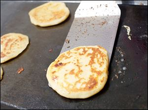 A pupusa, a traditional Salvadoran dish made of a thick, handmade corn tortilla stuffed with cheese or meat.