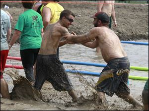 Spencer Woods, left, and Jason Eddinger try to push each other into the mud after their game during the Kidney Foundation mud volleyball tournament.
