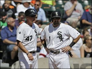 Chicago White Sox's Adam Eaton, right, is congratulated by third base coach Joe McEwing at third base.
