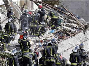 French firemen search in the rubble of  a building after an explosion collapsed it Sunday in Rosny-sous-Bois, outside Paris.