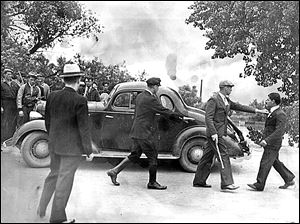 A group of vigilantes stop a car on the road to Monroe, Mich., while another one halts the vehicle's owner.  Every automobile attempting to enter Monroe  June 11, 1937, was stopped by armed vigilantes who are trying to keep sympathizers of the Newton Steel Co. strike from entering Monroe.