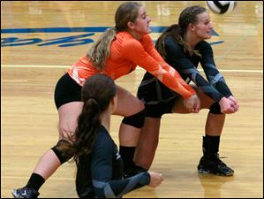 Otsego's Kylie Asmus, in orange, and Abby Hesselschwardt, right, both go for a serve.