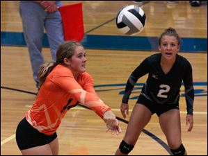Otsego's Kylie Asmus returns a serve in front of Alex Wenig.
