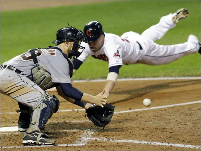 Detroit Tigers' Bryan Holaday, left, waits for the ball as Cleveland Indians' Jason Kipnis slides safely into home plate.