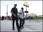 A protester is removed by police from blocking traffic near a McDonald's restaurant on Mack Avenue in Detroit.
