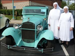 Sister Alice Marie and Ssiter Andrea stand by a 1932 Chevy.