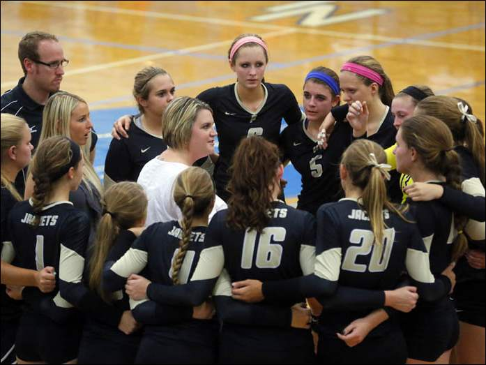 Perrysburg's coach Jamie Babcock leads her team from the center of a circle during a NLL volleyball match against Anthony Wayne