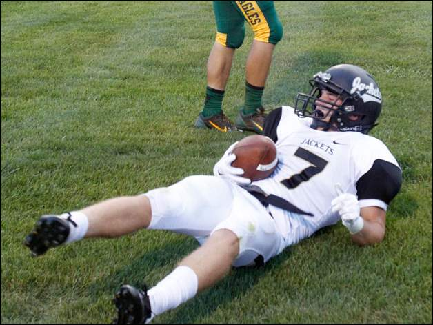 Perrysburg's Quinn Thomas sits on the ground after running into the end zone as Clay's Steven Nguyen stands next to him.