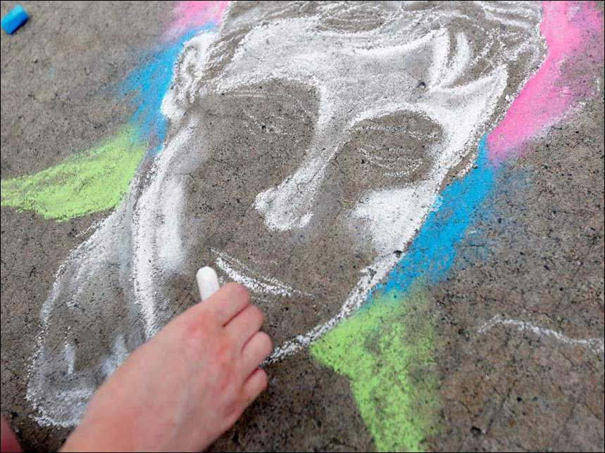 Jessie Counterman, of Bowling Green, draws a portrait of her best friend in chalk on Main Street during the 22nd annual Black Swamp Arts Festival.