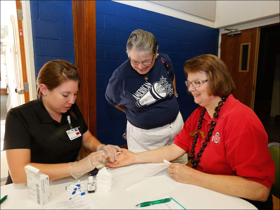 Wellness specialist Katrina Mock, from Promedica Wellness, left, performs a glucose screening on Jane Fausz, of Sylvania, at the health fair. Watching is Gayle Turner, of Toledo.