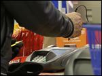 FILE - In this  Thursday, Nov. 28, 2013 file photo, a man pays with a credit card while shopping at KMart, in New York. The Federal Reserve reports on consumer borrowing for July 2014 on Monday, Sept. 8, 2014. (AP Photo/Julio Cortez, File)