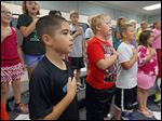 Andrew Mack, in a black shirt, joins Fort Meigs School fourth graders to rehearse the national anthem in music class for their performance in a Veterans' Day program.