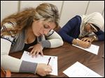 Sylvania Southview seniors Rosie Youssef, left, and Saraa El-Assir write letters as part of the students' Peace Project.