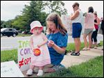Erin Shetler of Harvester, Mo., and her daughter, Amy, take a snack break during a rally to raise awareness for maternity care issues.