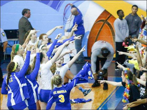 The St. Ursula volleyball team sings the school's Alma Mater with their fans.