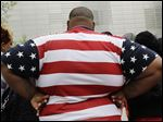 An overweight American man wears a shirt patterned after the American flag.