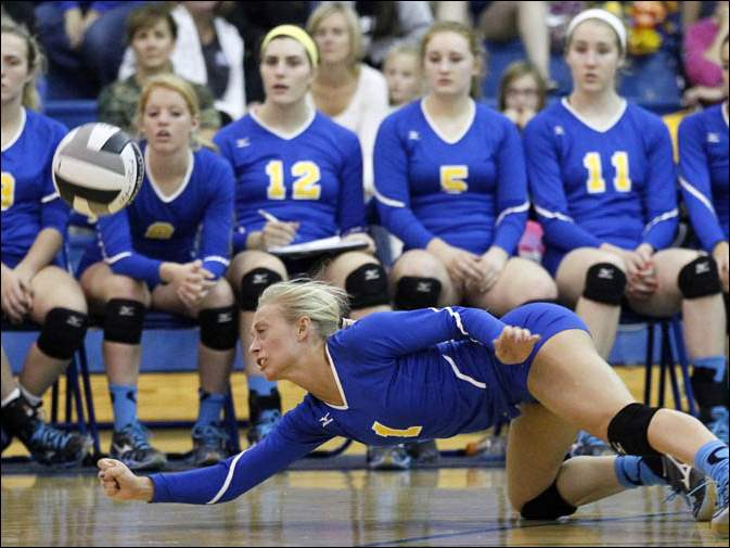 St. Ursula's Maurissa Leonard (1) returns a serve as her teammates watch from the bench.