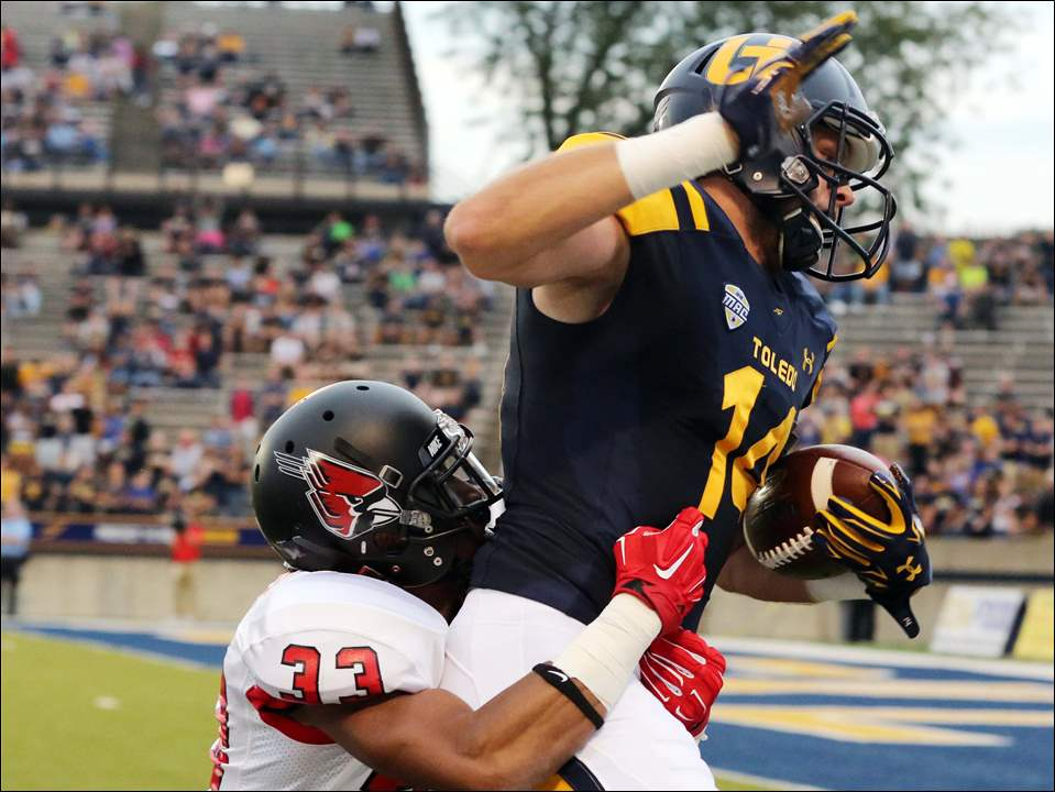 University of Toledo WR Justin Olack (14) makes a catch for a first down against Ball State CB Tyree Holder (33) during the first quarter.