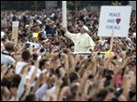 Pope Francis waves to faithful as he is driven through the crowd, in mother Teresa square, Sunday in Tirana.