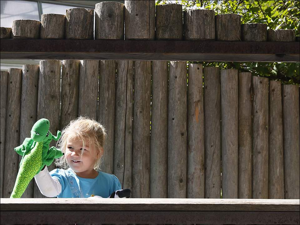 Lessa West, 3, from Milbury, performs a puppet show with the puppets available in the children's garden at The 577 Foundation.