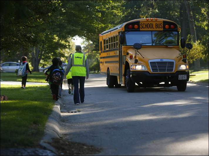 Jill Heine, with ProMedica, right, ushers Basil Moussa, 6, left, and other students down Gettysburg Dr. to join a group of  students on their way to Sylvan Elementary School.