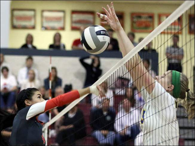 Central Catholic's Dani Tschantz (4) battles St. Ursula's Elizabeth Coli (15) at the net.