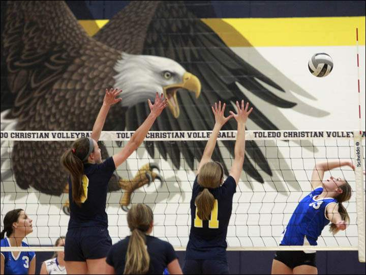 Tiffin Calvert's Alison Huss, far right, serves the ball against Toledo Christian.