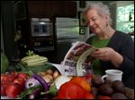 Paula Ross, co-founder of the Slow Food Maumee Valley chapter, looks over a cookbook in her home in Ottawa Hills.