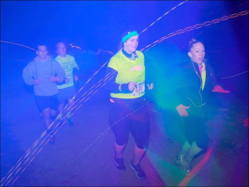 From right, Ashley Richardson of Maumee and Rachel Ade of Toledo run during the Glow Toledo/Run for Reece fundraising race at Woodlands Park.