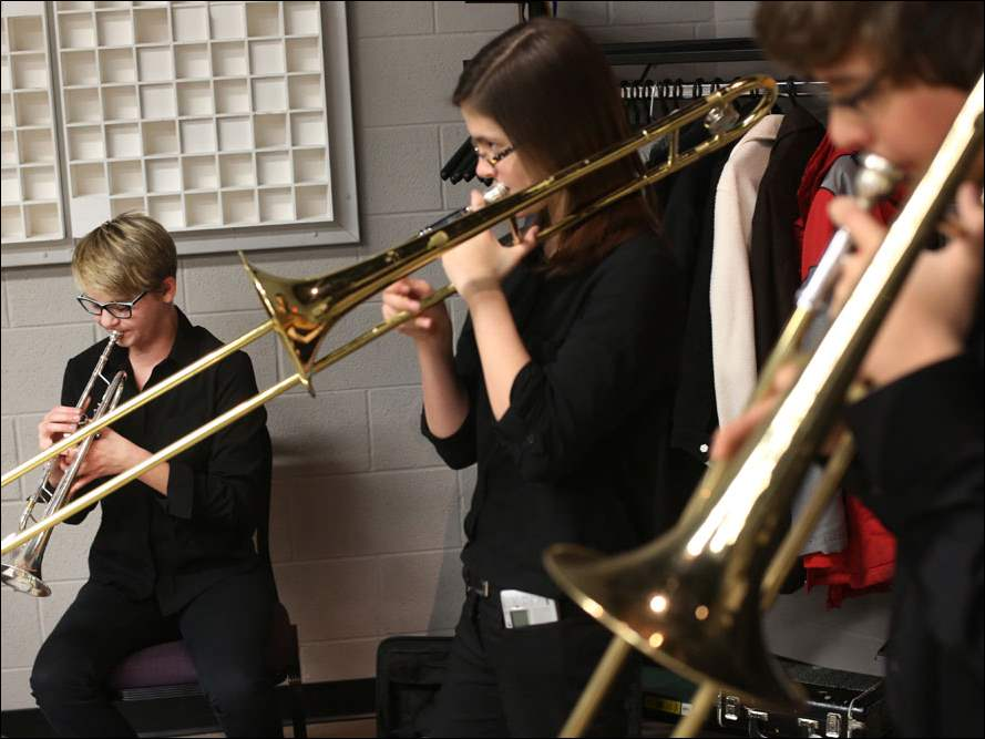 Lydia Kuhr, 14, left, warms up on her trumpet as her trombone playing classmates Lainie Roper, 14, center, and Alexander Luster, 14, right, do the same backstage before the start of the Fall Concert.