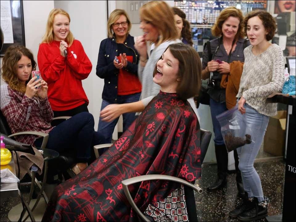 "Notre Dame Academy student Molly Martindale reacts to her new hair cut at Attitudes-A Salon in Sylvania, Ohio. Martindale is playing a male role in the school's production of ""Oliver!"" and wants to play the part. The other student who also cut her hair for a male role is Eileen DiPofi, right."
