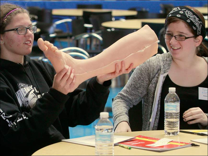 Perrysburg freshmen Lauren Christoff, left, and Anna Wyman get a close-up look at a leg created by LifeFormations.