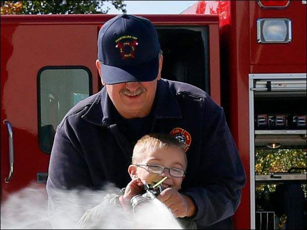 Perrysburg Township firefighter Steve Harrison helps Aiden Gomoll, 6, use a fire extinguisher to put out a contained fire.