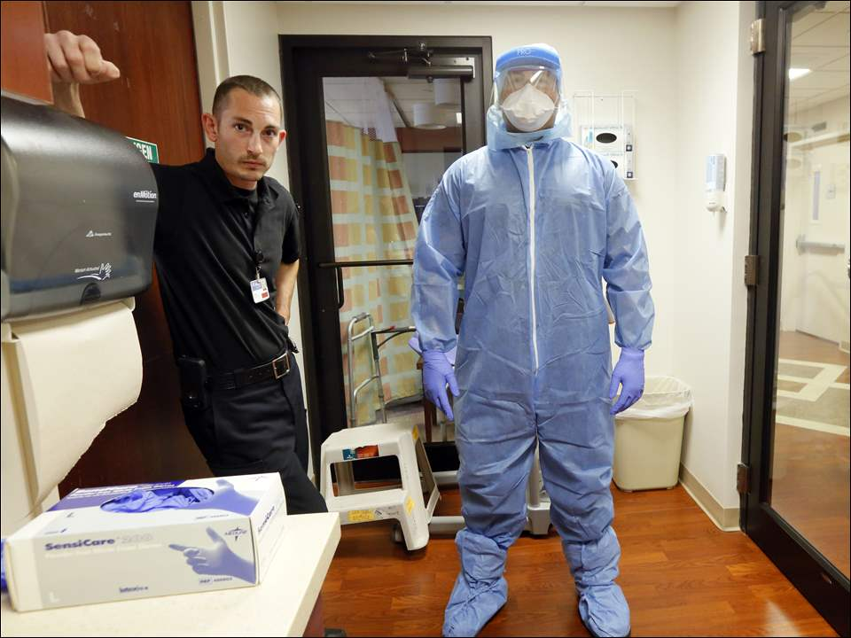 Chris Hofbauer, left, views David Abalos, right, in full Hazmat suit that health care workers must wear when treating Ebola infected patients at Mercy St. Vincent Hospital.