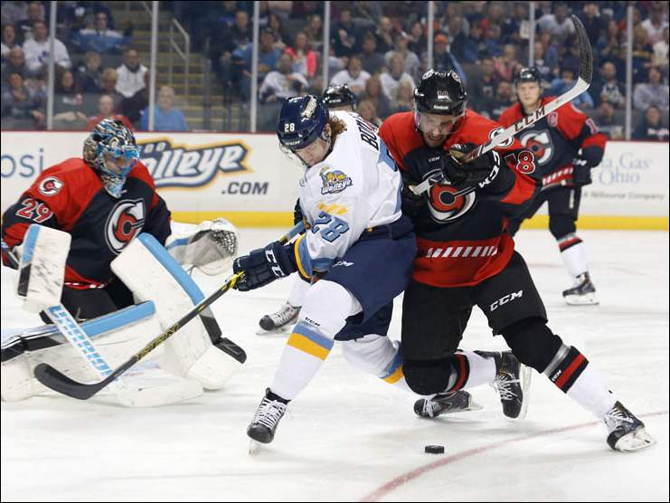Toledo Walleye player Kyle Bonis (28) fights for the puck with Cincinnati Cyclones player Wade Megan (18).