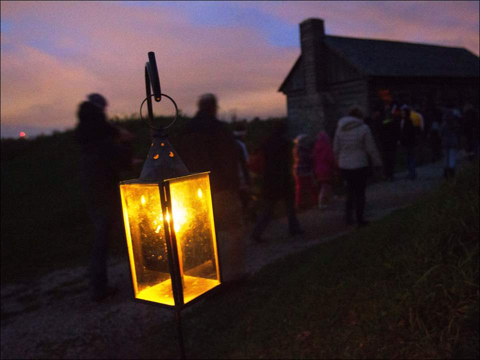 Ghost tour visitors walk past a lamp.