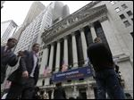 In this Oct. 2, 2014 photo, people pass the New York Stock Exchange, in New York. Stocks are opening mostly lower Monday, Oct. 20, 2014, as traders look over some disappointing corporate results. (AP Photo/Richard Drew)