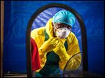 A healthcare worker dons protective gear before entering into an Ebola treatment center in the west of  Freetown, Sierra Leone, Thursday.
