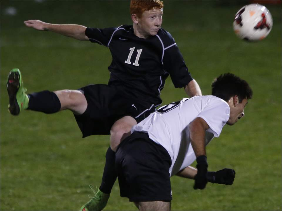 Perrysburg's Andrew Bosworth, 11, goes over Ashland's Will Van Scoy to put his head on the ball.
