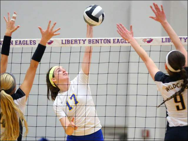 St. Ursula's Morgan Finn (17) spikes the ball against Northview's Kylee Keene (4) and Olivia Yoder (9).