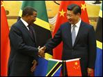 Chinese President Xi Jinping, right, shakes hands with his Tanzanian counterpart Jakaya Kikwete during a signing ceremony at the Great Hall of the People in Beijing, today.