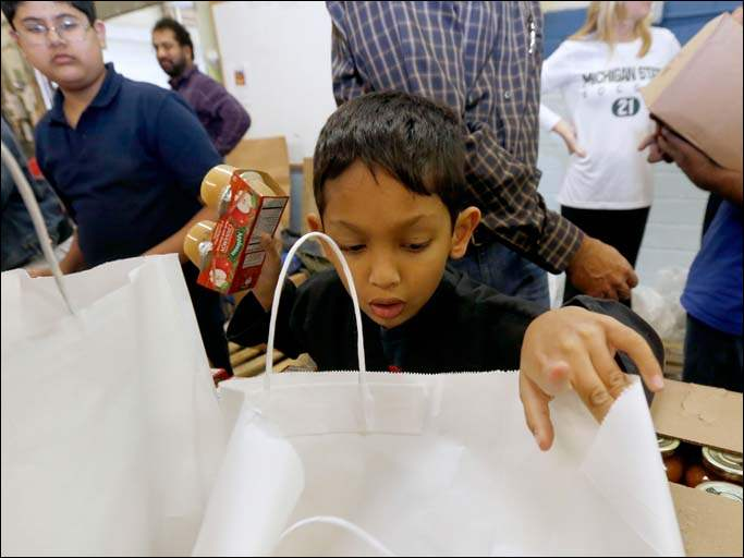 Raza Moghal, 6, puts apple sauce into bags during the Islamic Food Bank of Toledo's food drive.
