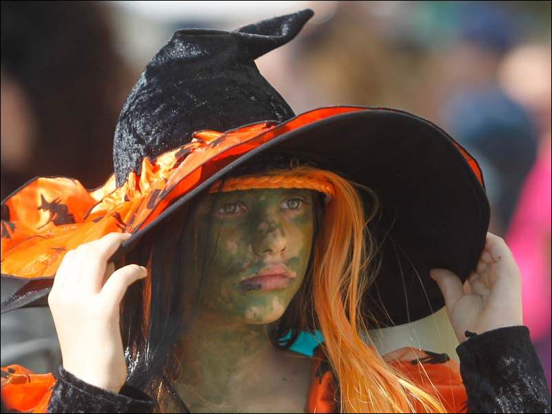 Destiny Maurer of Toledo, 10, adjusts her hat during a costume parade during the OctoBOOfest at downtown Perrysburg.